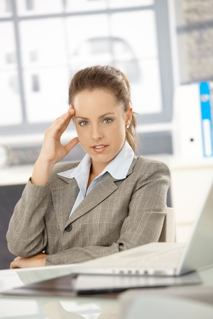 Young attractive businesswoman sitting at desk in office, looking tired. photo