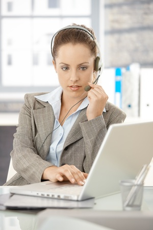 Young attractive dispatcher working in bright office, using headphones and laptop. photo