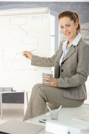 Young attractive businesswoman presenting in office, pointing, sitting on desk, smiling. photo