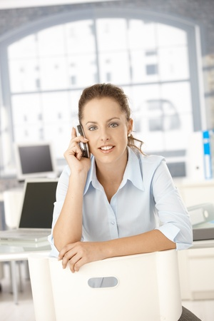Young attractive female sitting on conversed chair, talking on mobile phone, smiling. Stock Photo - 8747475
