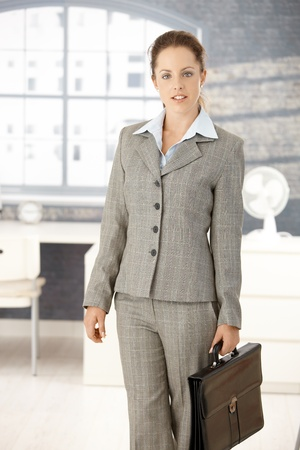 Attractive young businesswoman arriving to office in the morning, holding briefcase. photo