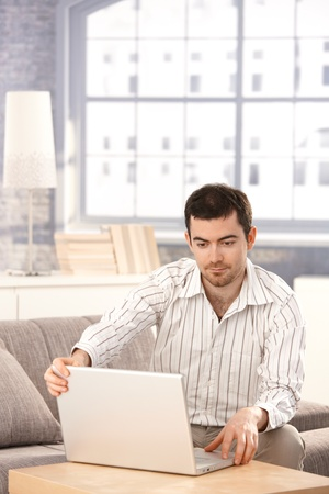 Young man browsing Internet at home, sitting on sofa, looking at screen. photo