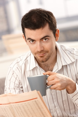 Young man reading newspaper, drinking tea at home in the morning. photo
