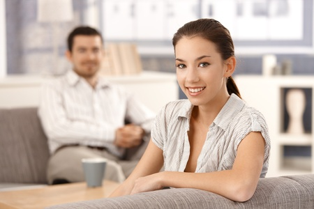 Young couple sitting in living room on sofa, smiling. photo