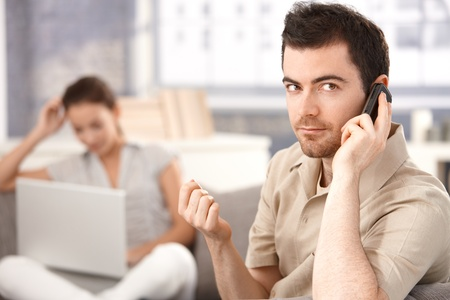 Young man sitting on sofa at home, talking on mobile, woman using laptop in the background. Stock Photo - 8747529