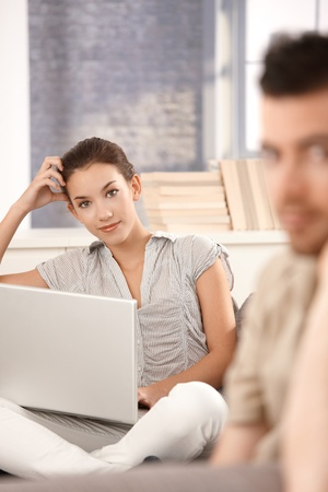 Young attractive woman using laptop at home, browsing internet, sitting on sofa, smiling, man in background. photo