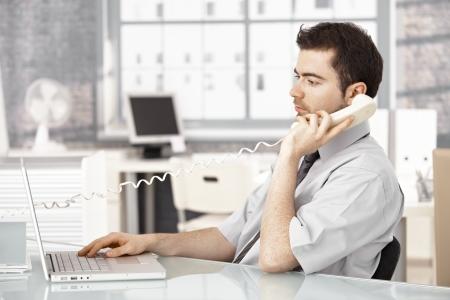 prestar atencion: Joven trabaja en la Oficina brillante, utilizando el portátil, hablando por teléfono.