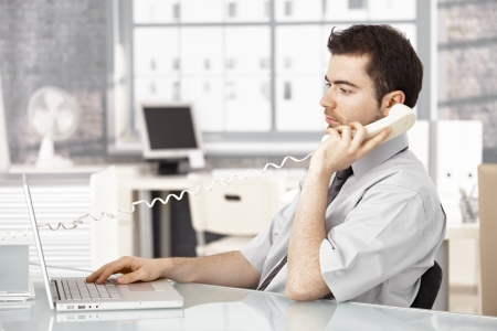 office window view: Young male working in bright office, using laptop, talking on phone. Stock Photo