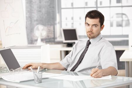 Young businessman working in bright office, using laptop, writing notes. photo