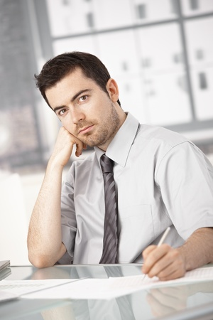 offish: Young businessman working in bright office, sitting at desk, writing notes, thinking.