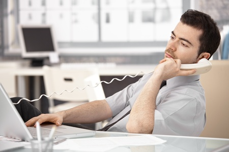 Young officer working in bright office, using laptop, talking on phone. Stock Photo - 8747500