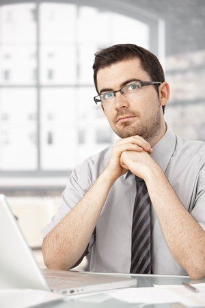 Portrait of young male sitting at desk, thinking, having laptop. photo