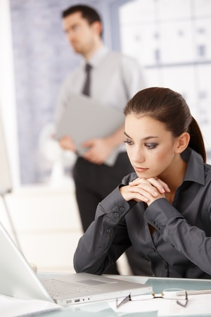 Young attractive woman sitting in office at desk, looking at laptop, man standing in background. photo