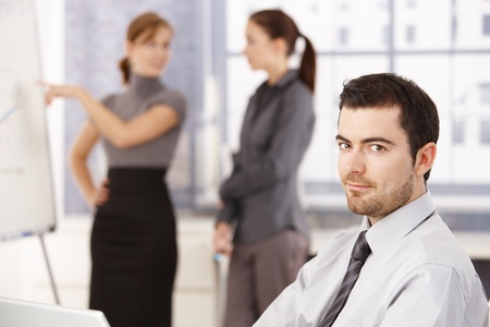 Young people working in bright office, man smiling in foreground, women chatting in background. Stock Photo - 8747486
