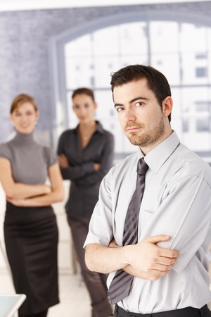Young people standing in office, man in foreground, women in background, arms crossed. Stock Photo - 8747518