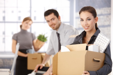 Happy team of businesspeople moving office, packing boxes, smiling. Stock fotó