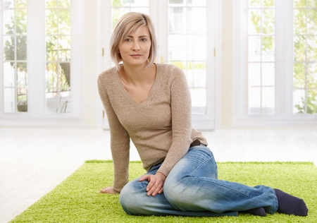 Portrait of attractive young blond woman sitting on floor at home looking at camera, smiling. Copy space for text. photo
