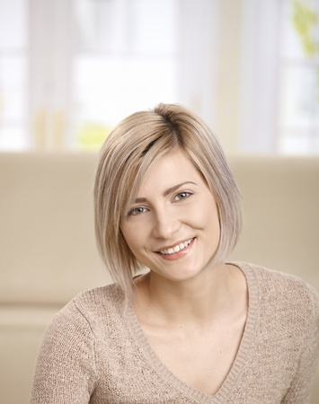 Portrait of smiling young blond woman at home, looking at camera, smiling. Copy space for text. Stock Photo - 8747856