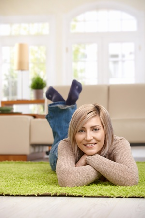 one mid adult woman only: Portrait of happy woman resting on floor at home, looking at camera, smiling.