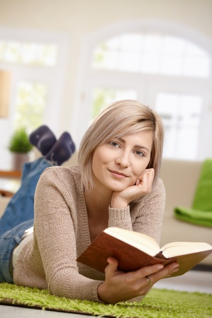 Young blonde woman lying on floor at home reading book, looking at camera, smiling. Copyspace above. photo