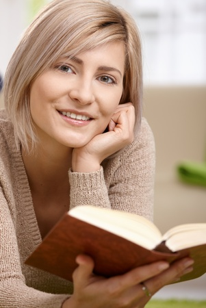 Young blonde woman lying on floor at home reading book, looking at camera, smiling. photo