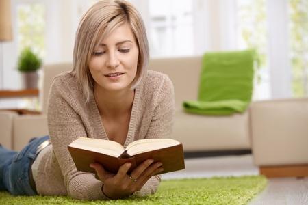 mujer leyendo libro: Rubia joven relajante en planta en casa de libro de lectura. Copyspace de derecha.