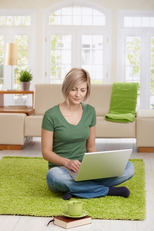 Smiling woman sitting on floor at home in living room using laptop computer for teleworking. photo