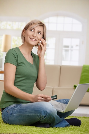 Woman arranging hotel reservation from home, using laptop, mobilephone and credit card.   photo