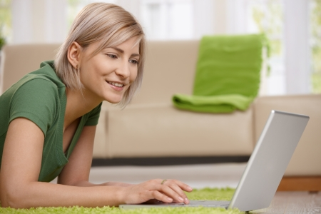 Young blond woman lying on floor at home working with with laptop computer. photo