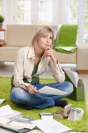 Worried woman thinking with paper in hand sitting on living room floor, checking documents,looking up, thinking. photo