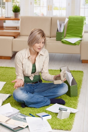 Woman checking documents and credit card account, shocked by financial situation, sitting at home on floor. photo