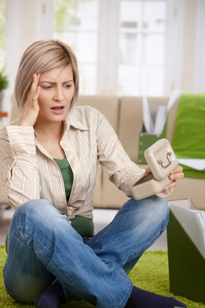 Shocked woman sitting at home looking at money box, looking troubled. photo