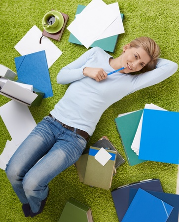 lay: Happy woman surrounded with documents lying on living room floor, daydreaming with hand under head.
