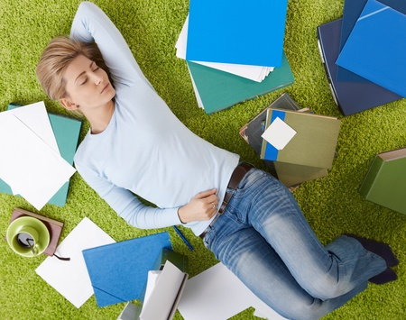 lay down: Pretty woman sleeping on floor surrounded with documents in living room floor,  with hand under head.