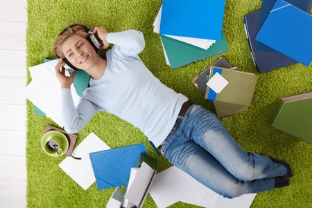 Smiling woman lying on floor listening to music with headset, surrounded with papers. photo