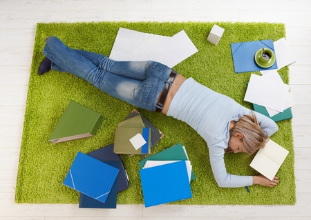 lying in front: Tired college student girl sleeping on floor at home. Stock Photo