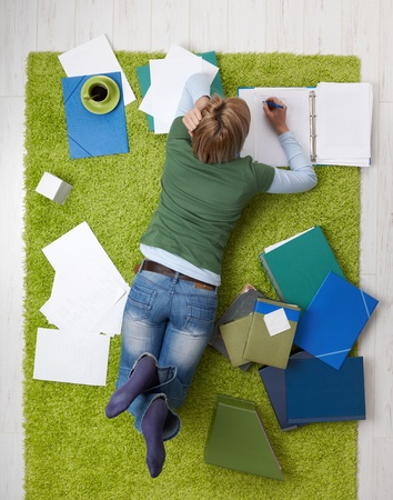 Young woman studying on living room floor, writing notes, having coffee. photo