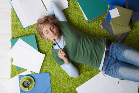Attractive young woman lying on floor with eyes closed, pen in hand, surrounded by books and notes, relaxing. photo