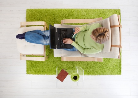 Overhead view of woman sitting in armchair shopping from home with computer and credit card. photo