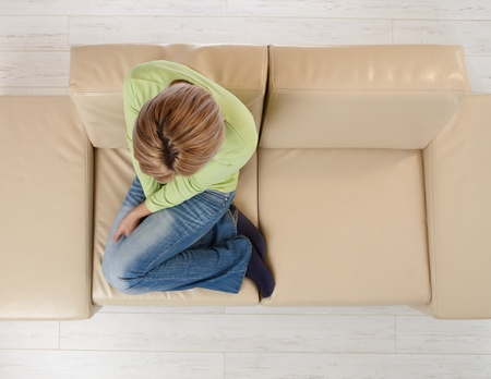 Woman sitting alone on beige couch with legs pulled up in high angle view. photo