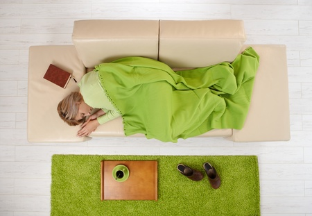 Woman napping on couch at home under blanket. photo