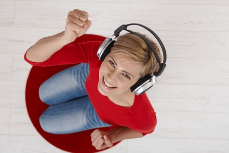 Woman with headphones looking up smiling with fists raised kneeling on round red carpet taken from overhead view. Stock Photo