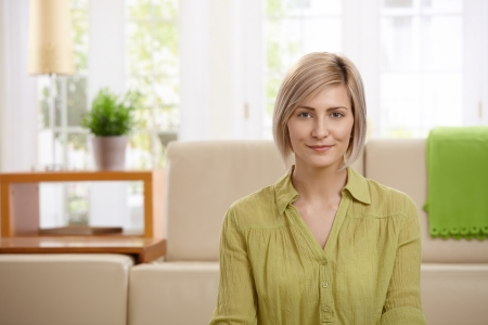 Portrait of attractive blonde woman smiling at home, sofa in background. photo