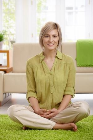 BUEN VIVIR: Feliz de mujer sentada con las piernas cruzadas en piso de la sala de estar, mirando la c�mara.