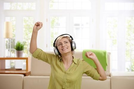 Woman having fun, enjoying music via headphones sitting at home with arms raised. photo