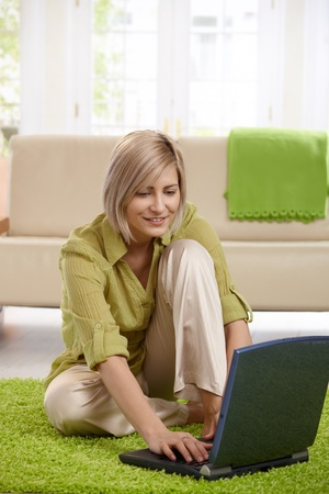 Smiling woman sitting on living room floor in front of sofa, working on laptop. Stock Photo - 8747899