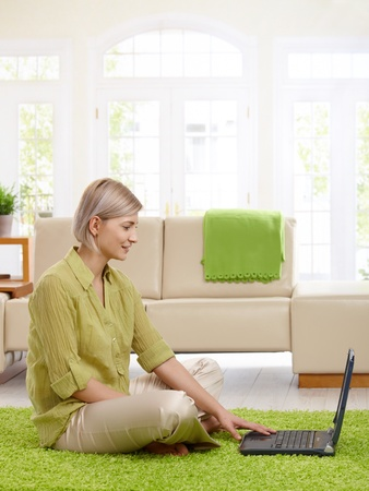 Attractive woman sitting on floor in living room looking at laptop.    photo