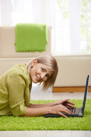 Smiling woman looking at camera, lying on floor of living room using computer. photo