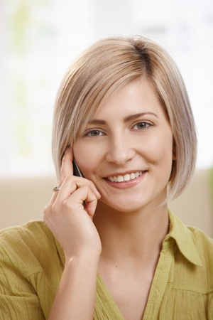 Portrait of attractive young woman speaking on mobile phone at home, smiling at camera. Copyspace on left. Stock Photo - 8747919