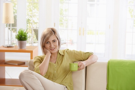 Smiling woman sitting on sofa in bright living room, holding coffee mug, looking at camera. photo